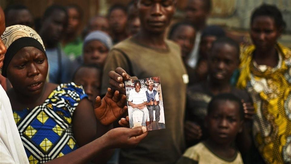 Une femme montre une photo avec un groupe de personnes en arrière