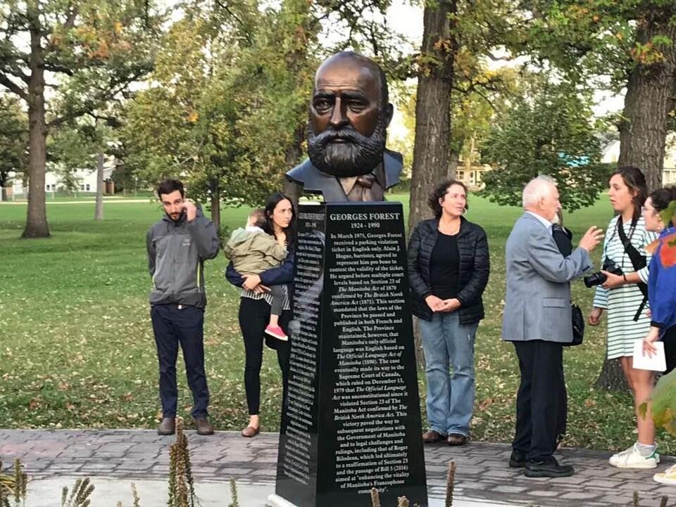 Des gens réunis autour du buste en bronze.