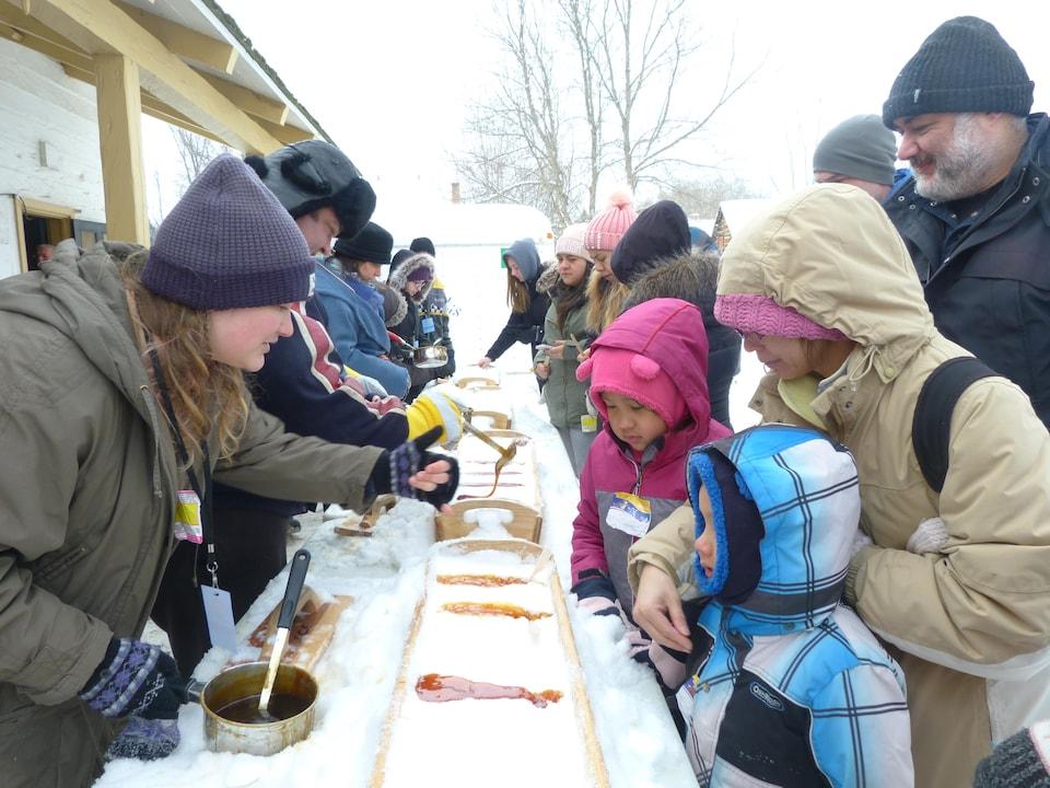 Des personnes versant de la tire d'érable sur de la neige pour les participants d'un carnaval.