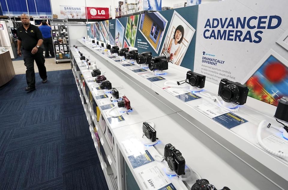 Un employé de Best Buy passe devant un étalage de caméras.
