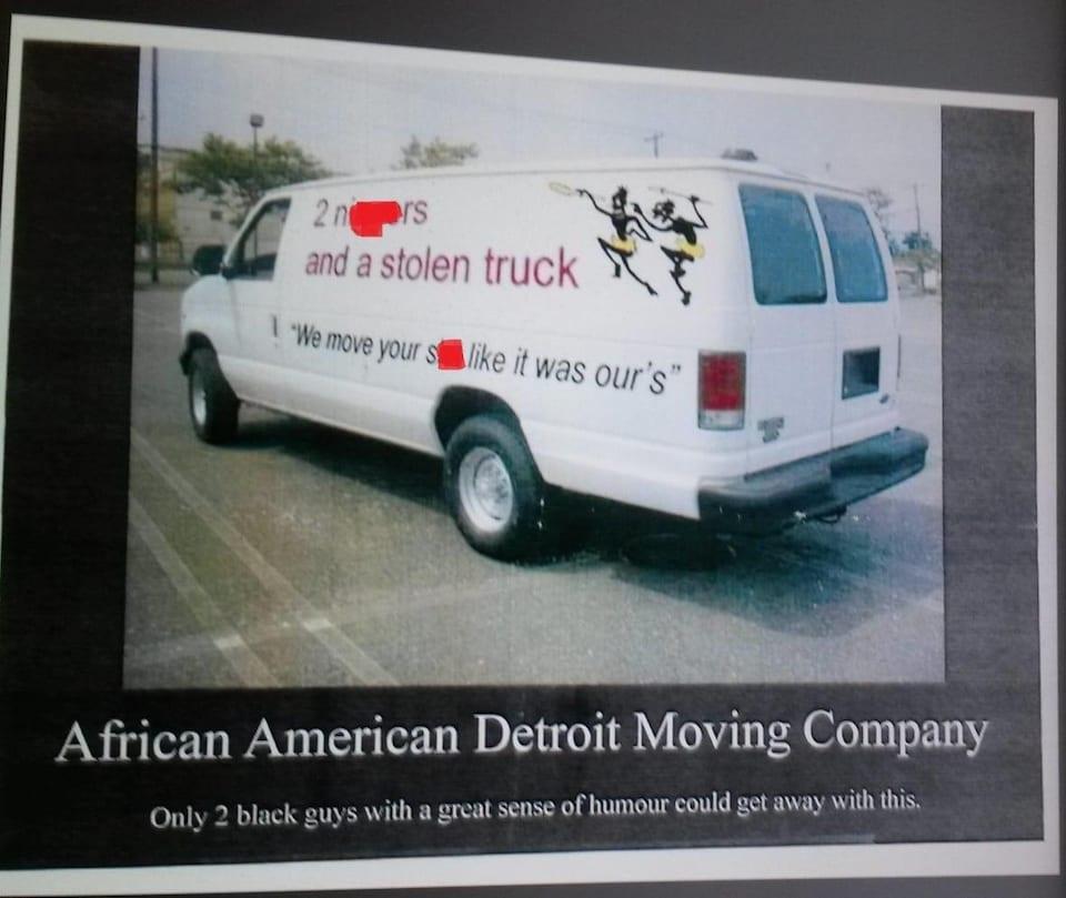 La camionnette blanche stationnée avec deux hommes noirs tenant des lances et des slogans offensants.