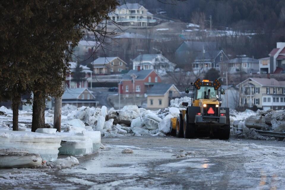 Un camion-chargeur tente de dégager des morceaux de glaces immenses accumulés sur la chaussée après que l'embâcle a cédé, mardi matin.