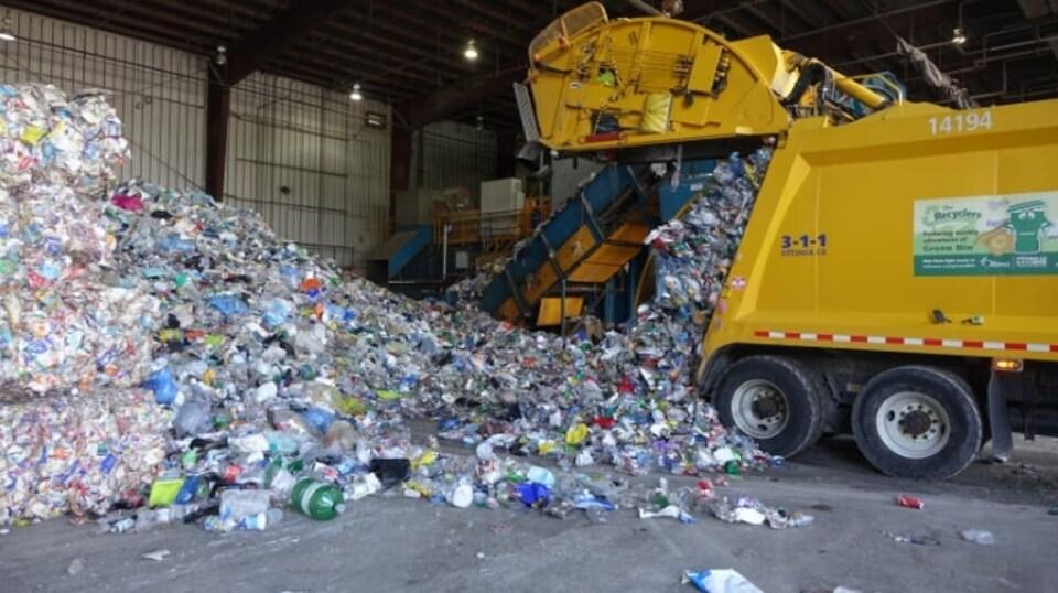 Un camion de recyclage jaune.