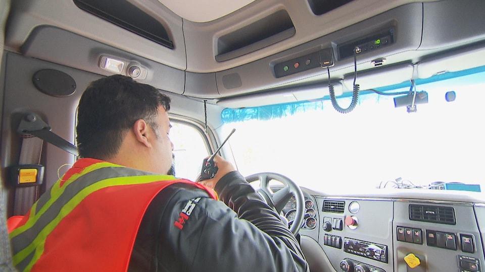 Un camionneur utilise la radio à ondes courtes pour signaler sa présence sur une route forestière en Haute-Mauricie.
