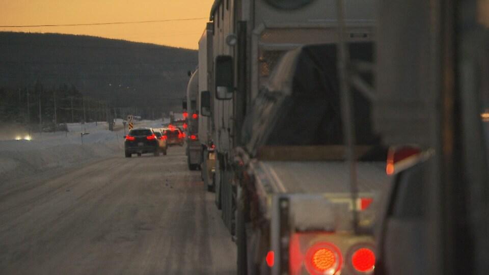 On voit une rangée de camions à droite et des véhicules à gauche.