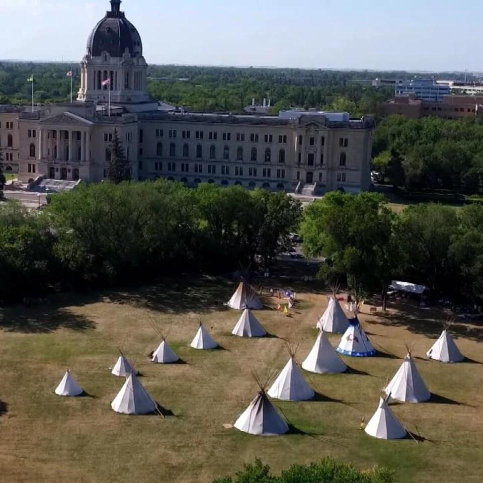 Vue aérienne d'un camp de tipis dans un parc, devant un grand bâtiment de style néo-classique.