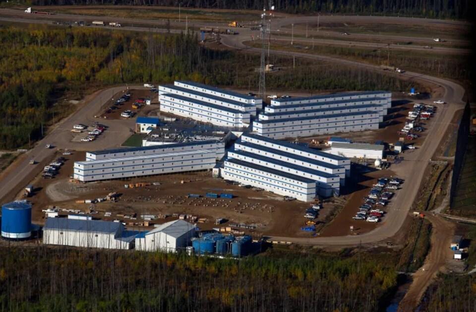 Quatre blocs de rangées de logements industriels identiques sont aménagés entre des routes et de la forêt.