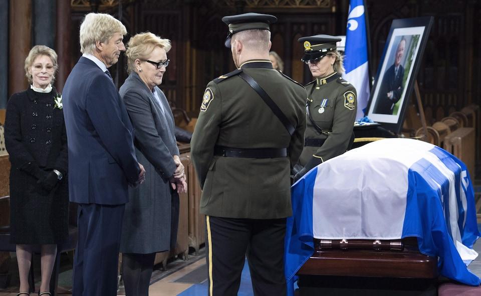 Un cercueil recouvert d'un drapeau, flanqué de deux policiers.