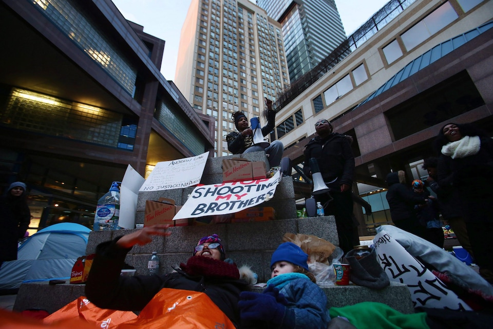 Protesters chant out front of the Toronto Police Headquarters in Toronto on Monday, March 21, 2016. A group of Black Lives Matter protesters have set up to occupy a space in front of Toronto Police HQ after the Special Investigations Unit cleared a Toronto police officer of any wrongdoing in the shooting death of 45-year-old Andrew Loku from this past July. THE CANADIAN PRESS/Cole Burston