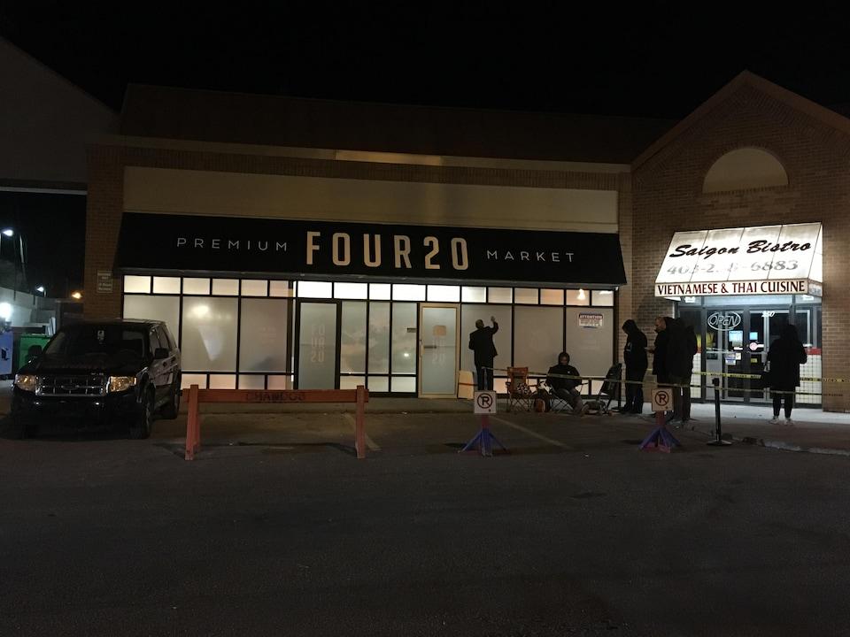 Il fait encore nuit sur le stationnement en face du Four20 Premium Market. Cinq personnes attendent devant l'entrée du magasin.