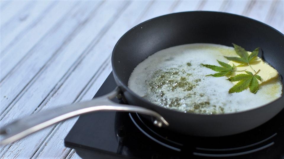 Des feuilles de cannabis nage dans du beurre, dans une poêle
