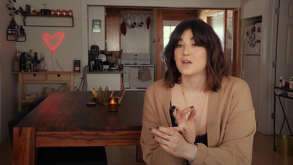 Une femme parle devant la caméra.