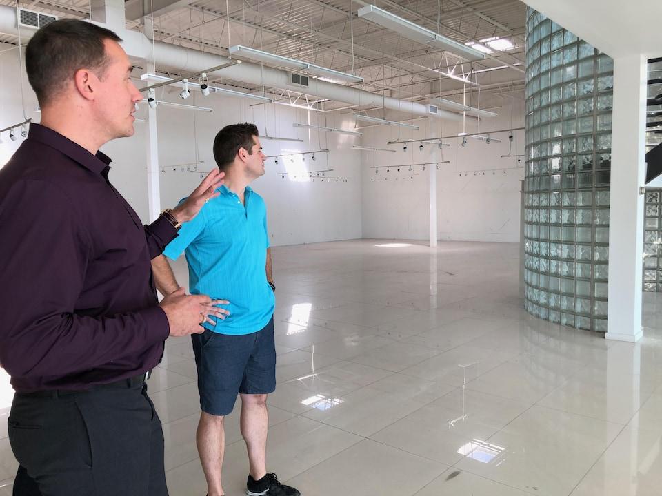 Deux jeunes hommes dans un entrepôts vide.