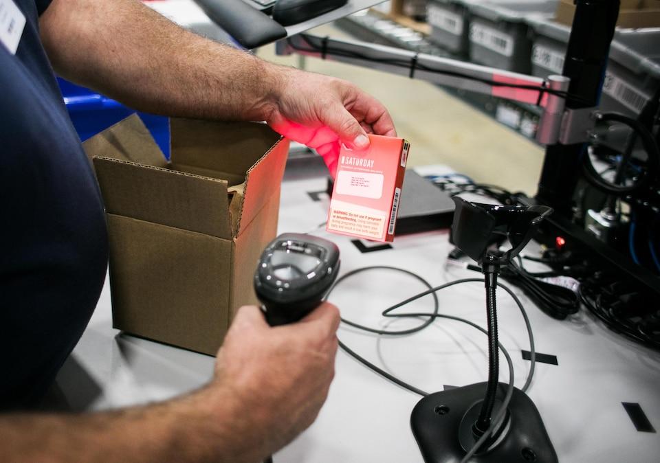 Un homme scannant un produit.