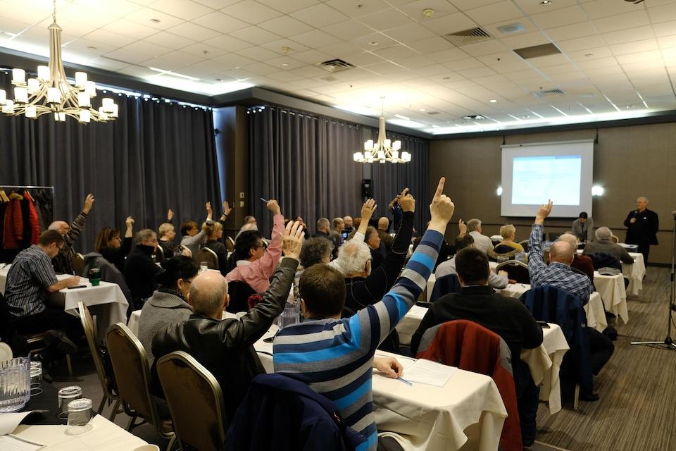 Des militants de la CAQ qui votent à main levée sur l'une des propositions.