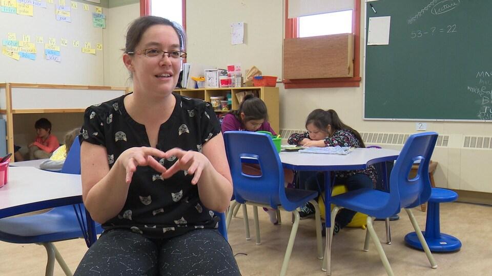Une enseignante accorde une entrevue à la caméra dans une salle de classe.
