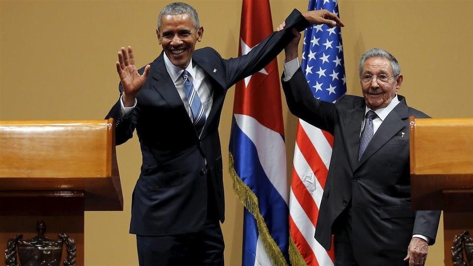 Le président cubain soulève le bras gauche de son homologue américain en lui tenant le poignet.