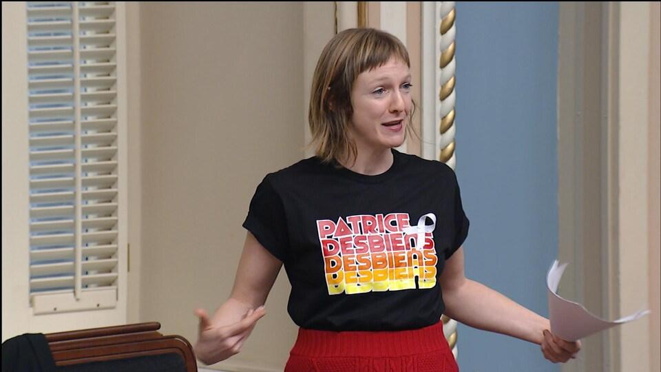 Catherine Dorion, à l'Assemblée nationale, est debout et porte un t-shirt sur lequel il est écrit Patrice Desbiens.