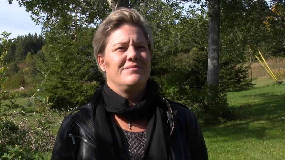 Cathy Poirier est près de quelques arbres et regarde au loin.