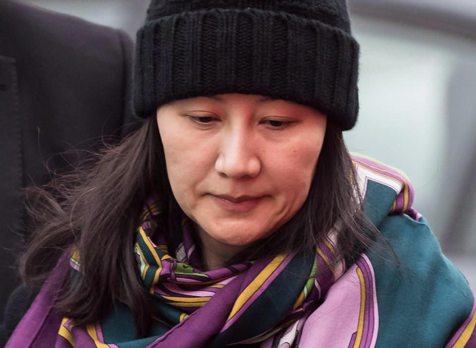 La directrice financière de Huawei, Meng Wanzhou, portant tuque et châle en compagnie d'un agent de sécurité à Vancouver, le 12 décembre 2018.