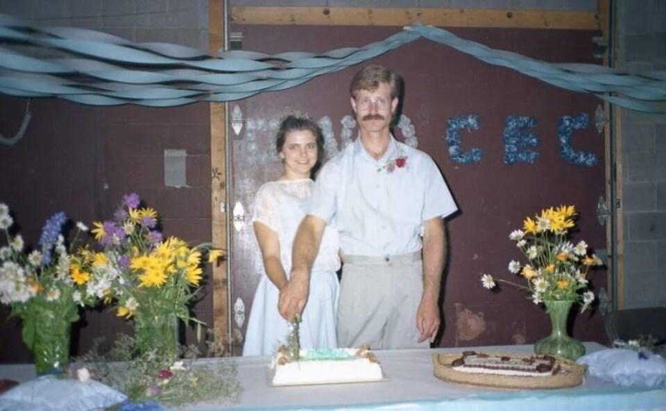 Les nouveaux mariés en train de couper leur gâteau de mariage.
