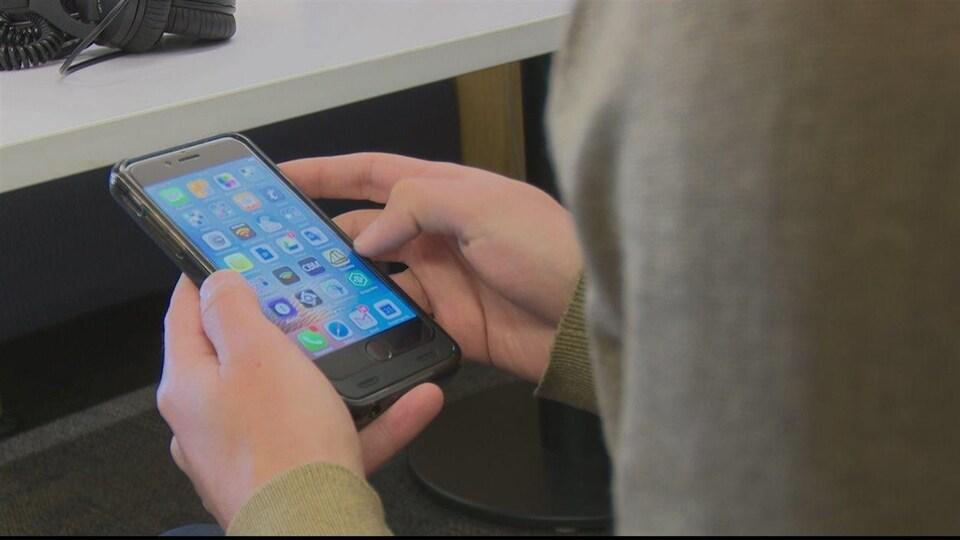 Un usager consulte son téléphone intelligent.