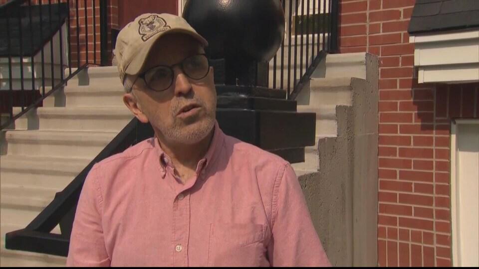 Un homme avec une barbe grise et une casquette, en entrevue