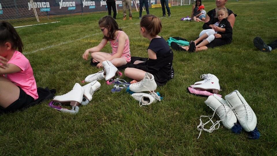 On voit des fillettes assises sur la pelouse. Des patins de patinage artistique se trouvent à leurs côtés.