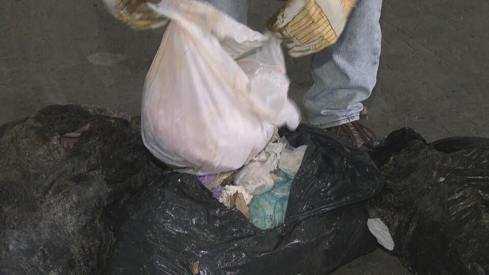 Un homme ouver des sacs d'ordures posés sur le sol.