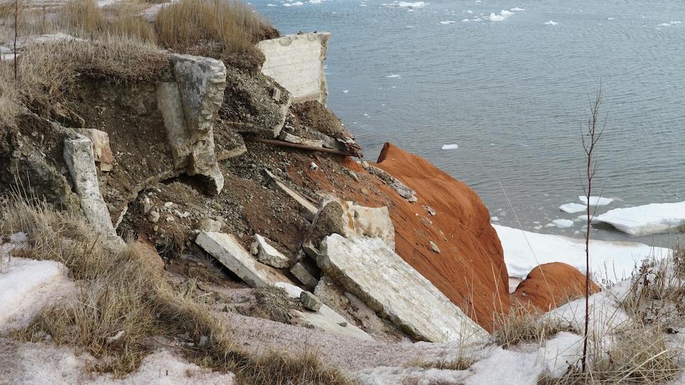 Débris de toutes sortes le long de la falaise du front de mer du centre-ville de Cap-aux-Meules, aux Îles-de-la-Madeleine, détruit par l'érosion.