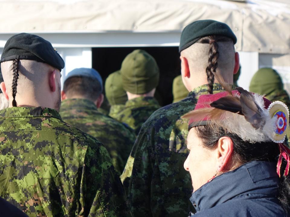 Deux militaires de dos, avec leurs tresses. À l'avant plan, une femme autochtone.