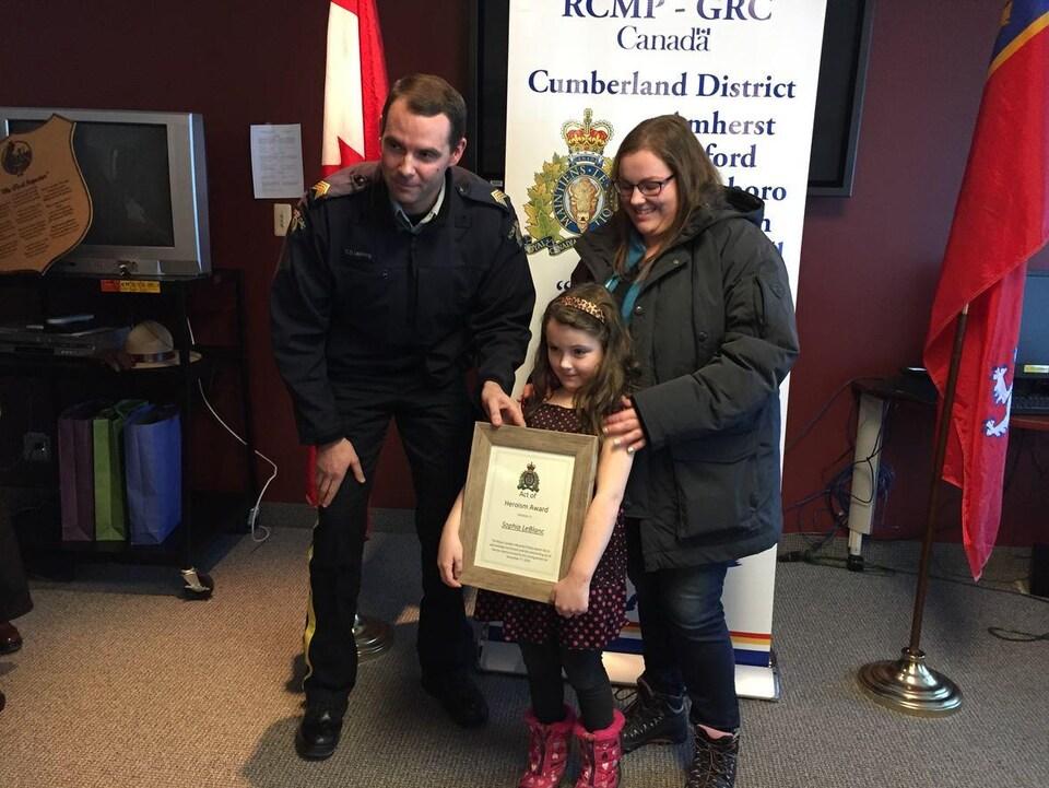Sophia pose avec son certificat, sa mère et un agent de la GRC.