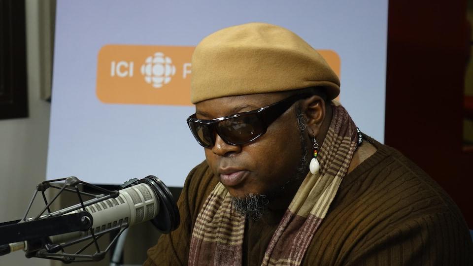 Un homme portant des lunettes de soleil et un béret derrière un micro
