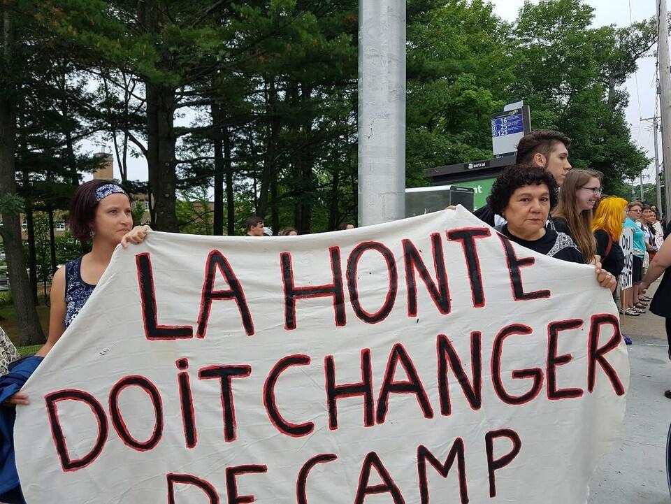 Des manifestantes et leur message intitulé «La honte doit changer de camp».