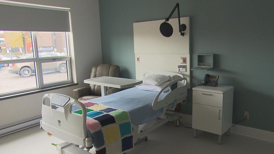 Chambre avec un lit motorisé et une grande fenêtre pour une personne en fin de vie