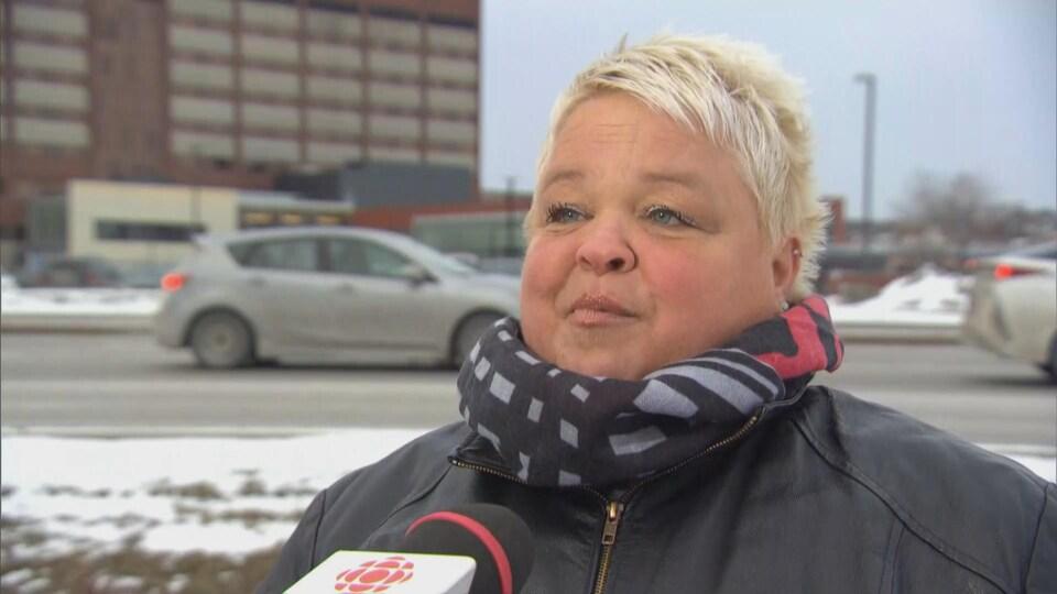 Une femme en entrevue devant une rue où des voitures circulent