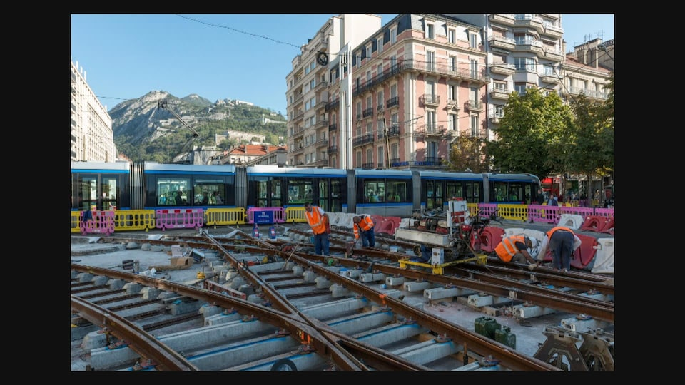 Chantier d'implantation du tramway à Grenoble. Des travailleurs mettent en place des rails
