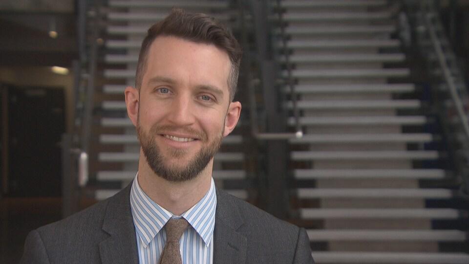 Une homme en complet souris à la caméra.