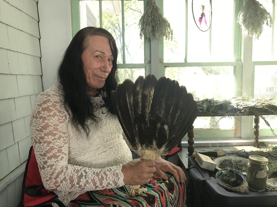 Une femme pose avec une plume d'aigle.