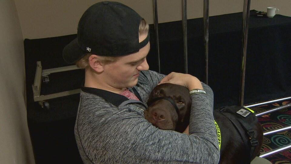 Un chien pose sa tête sur la poitrine d'un jeune homme portant une casquette à l'envers.