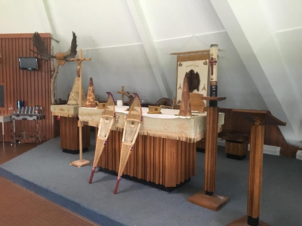 Des raquettes et des objets de chasse autochtones sont placés sur l'hôtel d'une église.