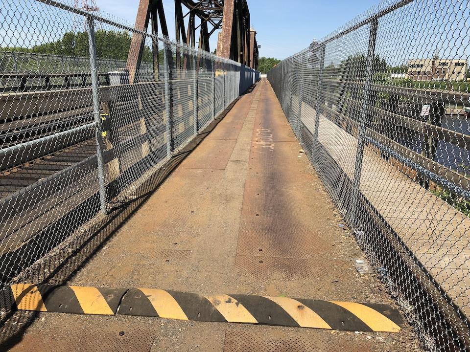 La voie réservé aux voitures sur un pont, recouverte de plaques de métal.