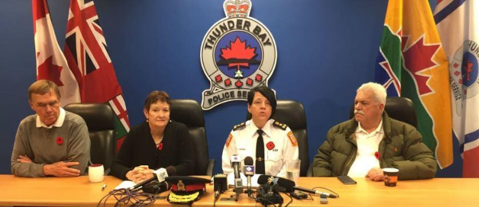 Trois personnes dans une conférence de presse.