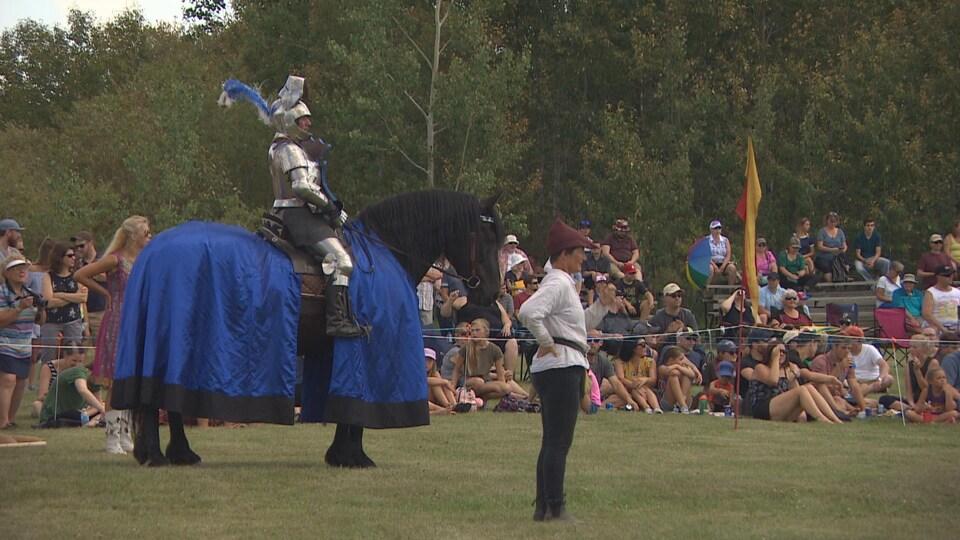 Un homme en armure monte un cheval noir sur lequel est posée une couverture bleue.