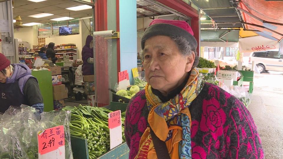 Hui Qing Chen et un marché derrière elle avec des légumes.