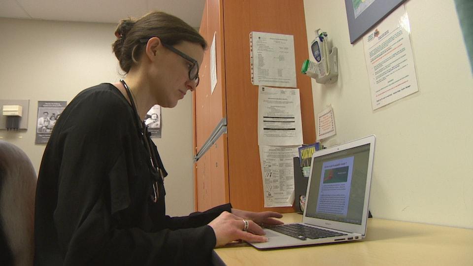 Allison Dart travaille, elle est devant un ordinateur.