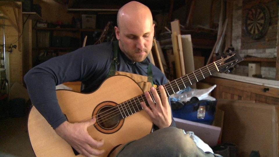 Le luthier franco-manitobain Christian Dupont joue sur une guitare qu'il a fabriquée.