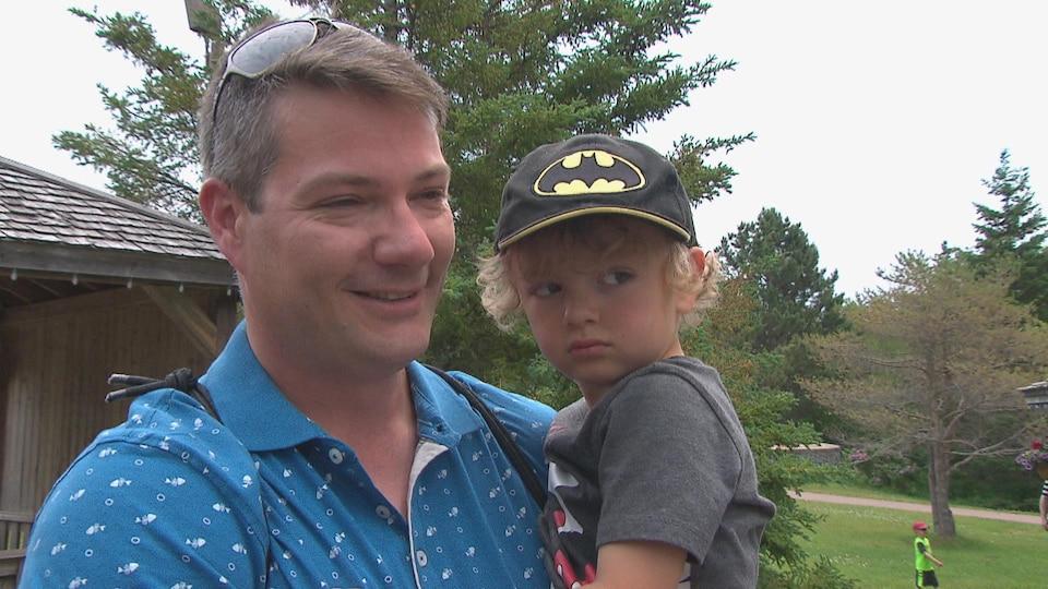 L'homme avec son petit garçon dans les bras.