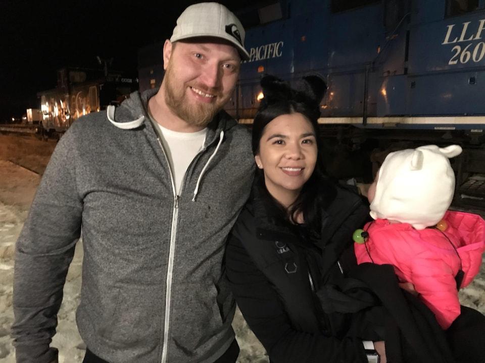 Adeelia Spence, résidente de Churchill, avec son compagnon et leur enfant devant un train à l'arrêt dans la nuit.