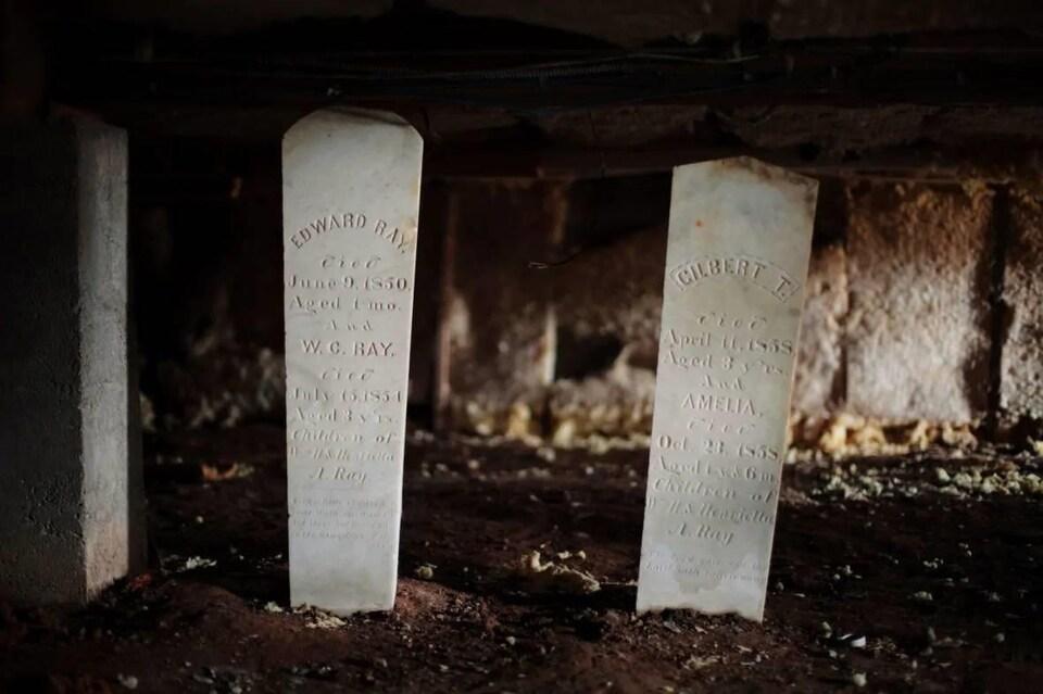 Deux pierres tombales blanches, portant les noms de quatre enfants en bas âge, dans un lieu sombre.